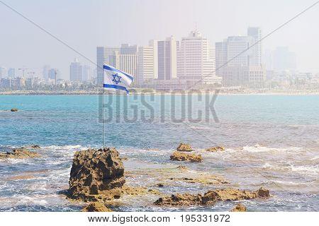 The flag of Israel against the background of modern Tel Aviv the Mediterranean Sea.