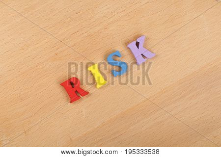 RISK word on wooden background composed from colorful abc alphabet block wooden letters, copy space for ad text. Learning english concept