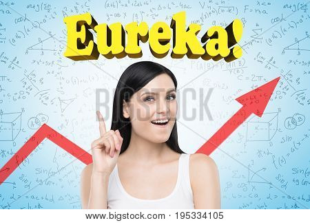 Portrait of a happy black haired woman wearing a white tank top and standing with a finger pointing up and crying eureka! near a blue wall with formulas on it and a red graph.