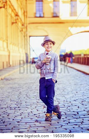 happy stylish boy with coffee in the city street