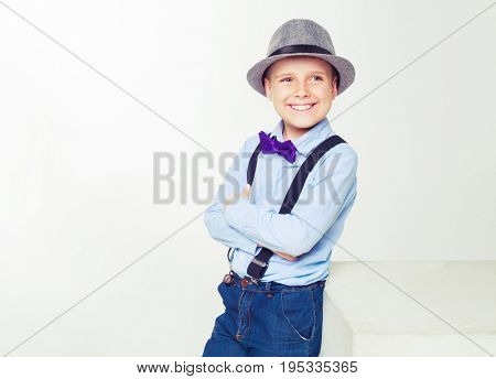 happy stylish boy wearing a hat, isolated against white background