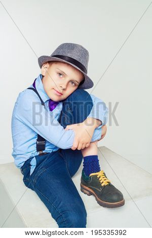 happy stylish boy wearing a hat and a tie, against white background