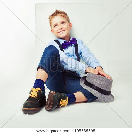 cheerful happy boy wearing a hat and tie, isolated against white