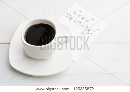 Simple Morning With White Cup Of Coffee For Better Half With 'good Morning' Message On White Wooden