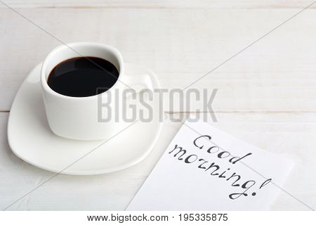 A Cup Of Coffee With Message 'good Morning' On White Wooden Table
