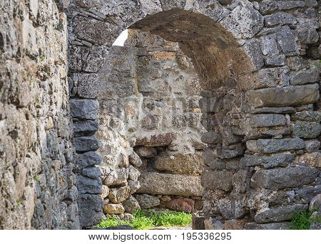 arch of gray stone old building way out of it on a stone masonry labyrinth amid the ruins