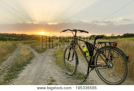 The bicycle stands on a village road that is divided into two parts. Sunset time.
