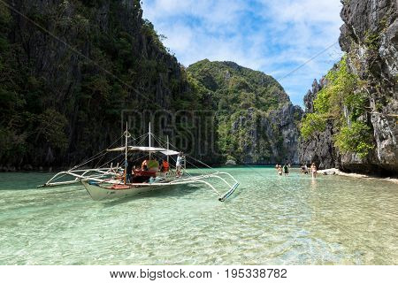EL NIDO PALAWAN PHILIPPINES - JANUARY 17 2017: Wide angle picture of a boat and tourists in the beautiful day in El Nido.