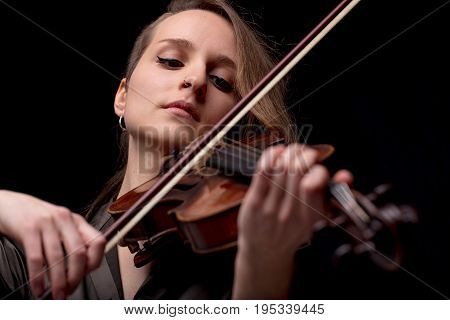 Serious Pretty Woman Playing Violin On Black