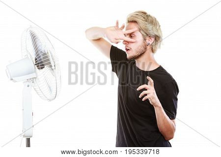 Young Man Fighting With Wind From Cooling Fan