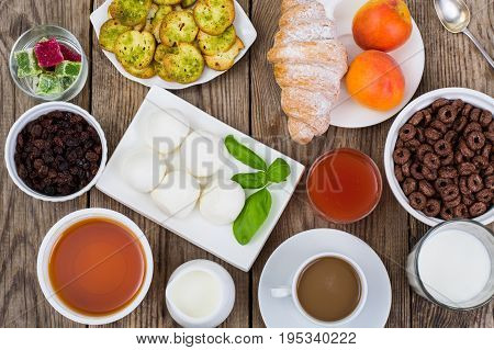 Breakfast table setting with  chocolate flakes, mozzarella,  juice, croissant, coffee, honey, raisins. Old wooden background, top view. Studio Photo