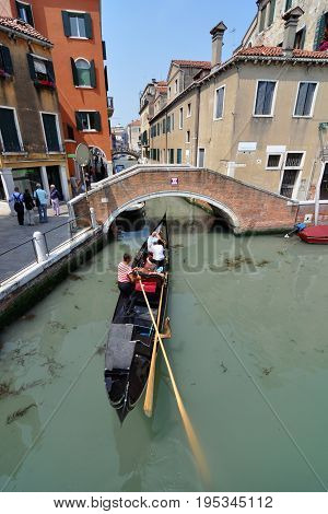 VENICE, ITALY - May 20, 2011 - A gondolier in Venice navigates his gondola through one of the city's many canals