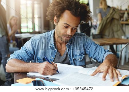 Portrait Of Smart Hardworking Ambitious Afro American Student Sitting At University Canteen, Working