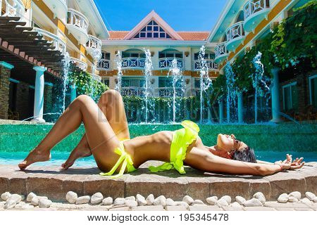 Sexy beautiful girl in bikini at the pool in the hotel. Summer vacation concept.