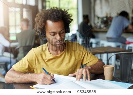 Fashionable African American University Student Doing Homework On French At Cafeteria, Studying Pron