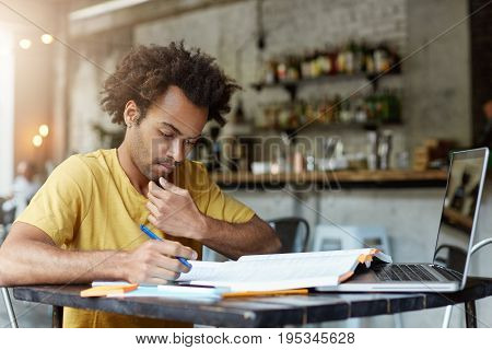Solemn Dark-skinned African American Student At His Workplace Looking In His Copy Book Writing Notes