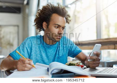 Candid Shot Of Handsome Stylish Black Student Of Law School Writing Down In Copybook While Doing Hom