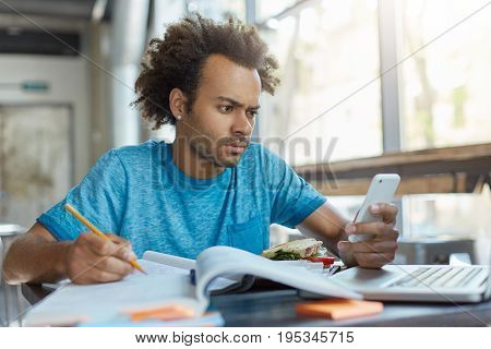 Stylish Handsome Guy With Dark Skin Sitting At Cafeteria Writing Something In His Textbook Holding C