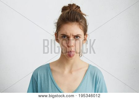 Angry Young Female Showing Her Digust And Distaste Having Gloomy Expression Demonstaring Tongue Refu
