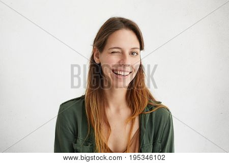 Portrait Of Beautiful Woman With Long Hair Winking While Having Good Mood Smiling Showing Her White