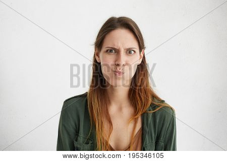 Attractive Female In Green Casual Clothes Sulking. Irritated Female Making Grimace Staring At Camera