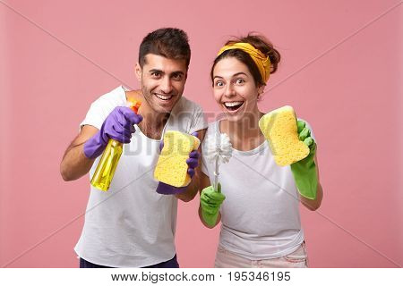 Excited Happy Young Male And Female Wearing Rubber Gloves, Holding Cleaning Supplies While Tidying U
