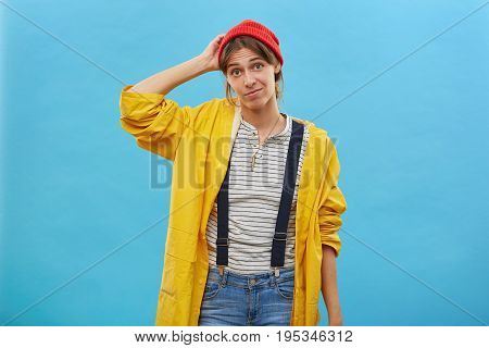 Portrait Of Doubtful Female Dressed Casually Scratching Her Head With Hand Not Knowing What To Do Is