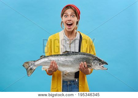 Wife Of Fisherman Holding Huge Fish Having Surprised Expression Looking With Bugged Eyes And Jaw Dro