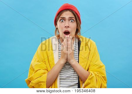 Headshot Of Amazed Emotional Young Female In Yellow Raincoat And Red Hat Posing Against Blank Blue W