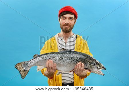 Bearded Fisherman In Yellow Anorak And Red Hat Holding Huge Fish In Hands, Demonstrating His Success