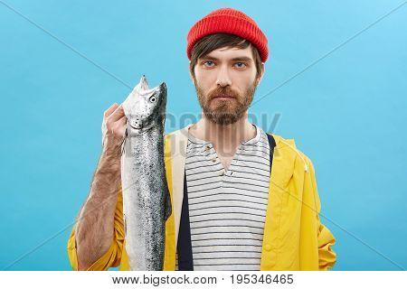 Indoor Shot Of Handsome Young European Fisherman With Beard Showing His Catch After Fishing Excursio
