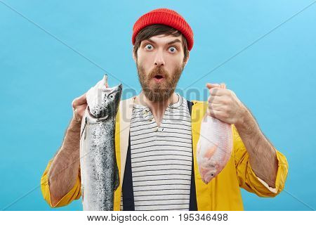 Human Facial Expressions, Emotions And Feelings. Funny Astonished Young Fisherman Wearing Red Hat An