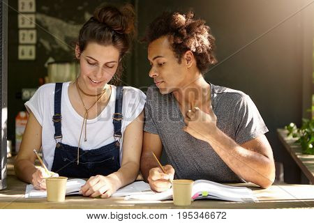 Two Mixed Race Students Sitting In Coffee Shop Drinking Takeaway Coffee Reading Books And Writing No