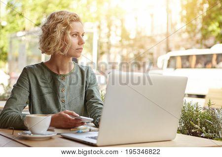 Portrait Of Dreamy Businesswoman With Wavy Blonde Hair Sitting At Outdoor Restaurant Drinking Coffee