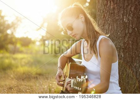 Outdoor Portrait Of Young Teenage Female Dressed Casually Wearing Trendy Sunglasses Playing Guitar W