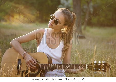 Caucasian Female With Dark Hair Tied In Pony Tail Wearing Sunglasses And White Shirt Playing Guitar