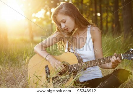 Young Girl With Luxurious Hair Dressed In White Shirt Sitting Crossed Legs Alone At Green Grass Lear