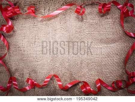 red ribbon frame on brown fabric background