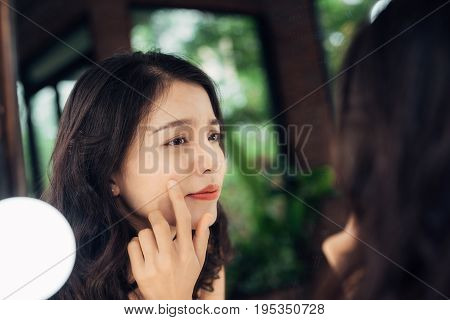 Beauty skin care lifestyle concept. Young asian woman with acne looking at the mirror.