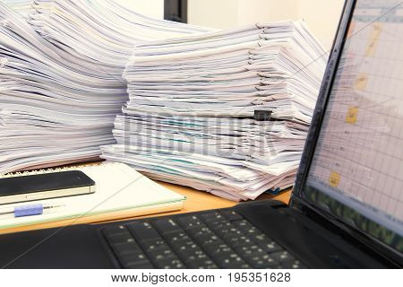 Computer Notebook And Documents On Desk Stack Up High Waiting To Be Managed