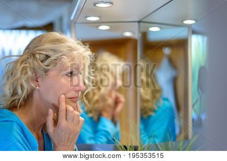 Senior Blond Woman Checking Her Ageing Skin