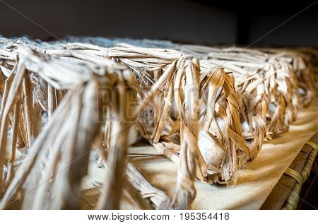 Suzhou, China - Nov 5, 2016: At Suzhou Number 1 Silk Factory; silkworm cocoons being nurtured in straw cage. Low-light and shallow depth of field image.