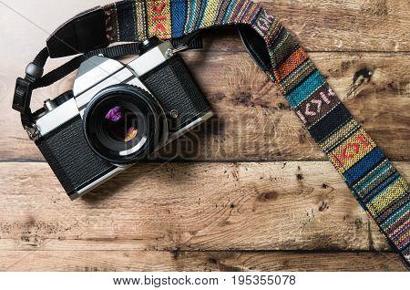 Old analog camera with vintage strap on a wooden desk