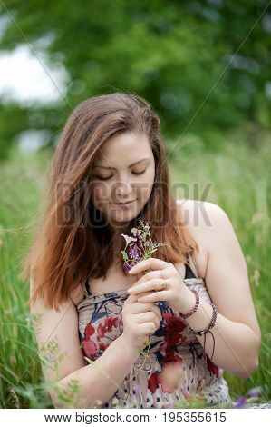 Portrait pretty young long-haired woman holding bouquet wildflowers background green meadow