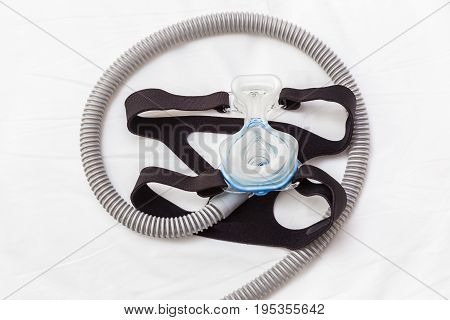 CPAP mask connecting with strap and hose laying on a bed for helping snoring people with respiratory problem