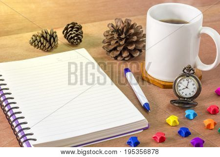 Black coffee with a notebook on a brown table. In the morning and Vintage clock at 8 o'clock. Paper stars and pine cones laid on wooden table.