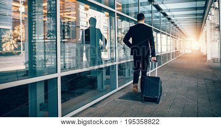 Businessman Walking Outside Public Transport Building With Lugga