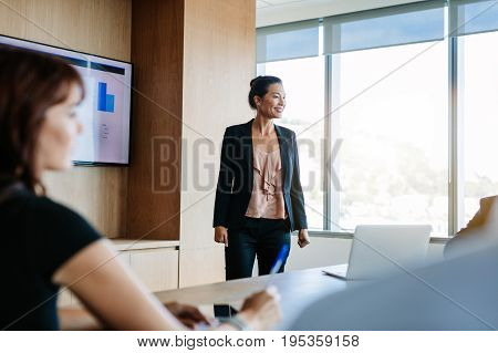 Asian businesswoman explaining plans to colleagues in conference room. Business presentation in board room.