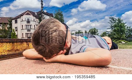 Playground relaxation, little boy looking at the blue sky in sung-lasses, lying on a table tennis table