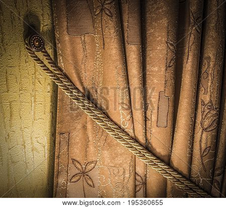 Detail of brown curtains close-up with artificial lighting.
